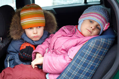 The sad boy with the little girl, in winter clothes in the car. photo