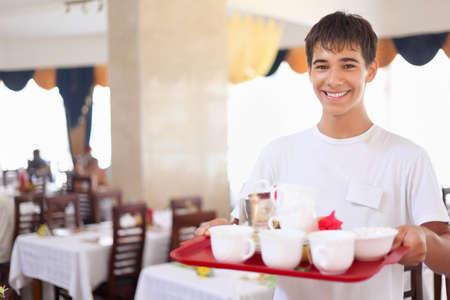 meseros: joven camarero afable sonriente mantiene bandeja con platos en el restaurante, gran angular Foto de archivo