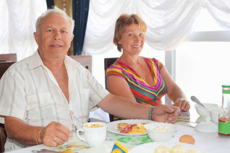 Smiling elderly married couple having breakfast at restaurant near window photo