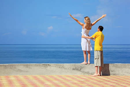 young man and beautiful woman on quay, woman lifted hands upwards  photo
