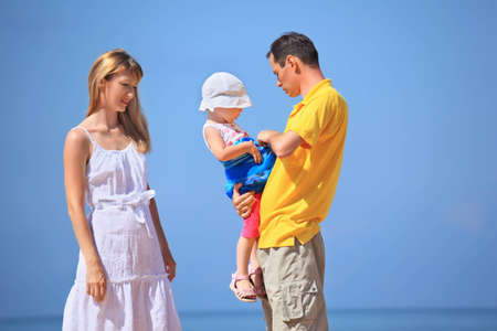 Happy family with little girl in white hat against sea Stock Photo - 9112302