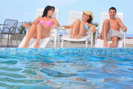 Smiling man and two young women reclining on chaise lounges near pool open-air, wide angle photo