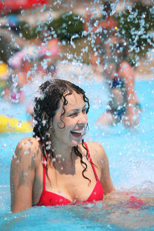 Smiling beautiful woman bathes in pool under water splashes Stock Photo - 9265015