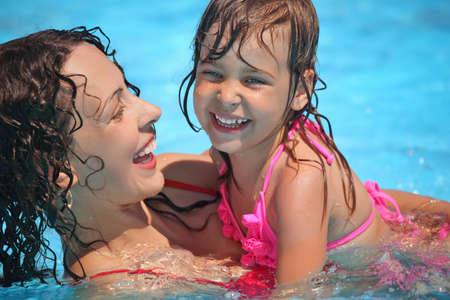 one family: Smiling beautiful woman and little girl bathes in pool