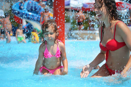 child girl nude: Smiling beautiful woman and little girl bathes in pool under water splashes Stock Photo