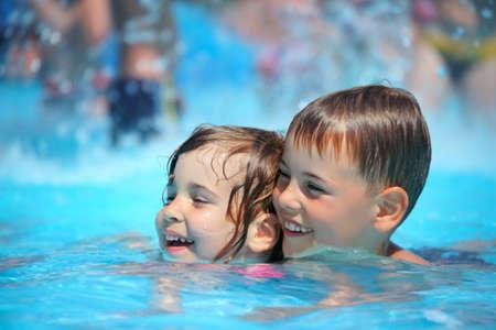 meisje zwemmen: Lachende jongen en meisje zwemmen in zwembad in aquapark Stockfoto