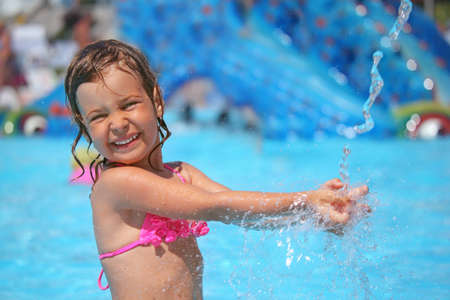 little girl bathes in pool under water splashes in aquapark photo