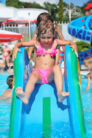 pretty little girl goes down on hill in aquapark of an entertaining complex Stock Photo - 9265014