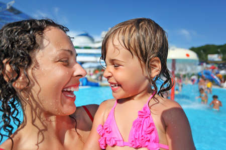 Smiling beautiful woman and little girl bathing in pool of an entertaining complex, Looking against each other Stock Photo - 9265019