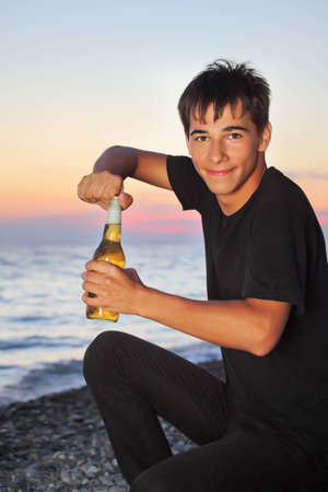 teenager boy opens beer bottler on stone seacoast in evening Stock Photo - 9264962
