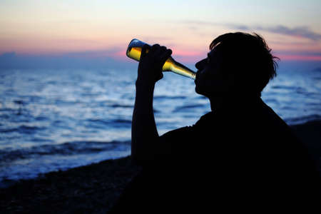 Silhouette teenager boy drinking beer on stone seacoast in evening photo