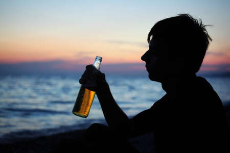 Silhouette teenager boy with beer bottler on stone seacoast in evening photo
