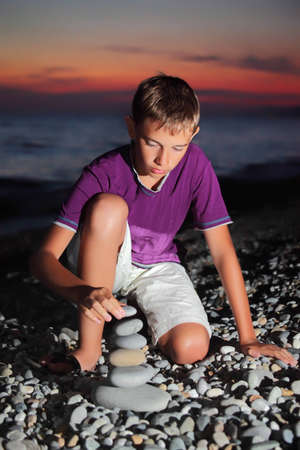teenager boy creates pyramid from pebble on stony seacoast at night photo