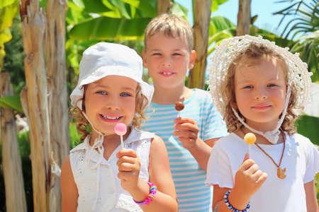 cousin: Smiling children three together eat lollipop in park