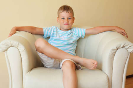 boy freely sitting with magnificent easy chair in cosy room Stock Photo - 9264904