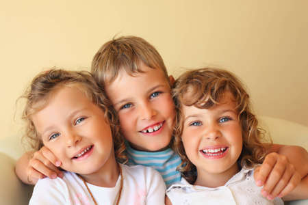Laughing children three together in cosy room, two pretty girls and boy Stock Photo - 9264978