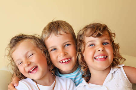 Smiling children three together in cosy, girl at left closed eyes Stock Photo - 9264987