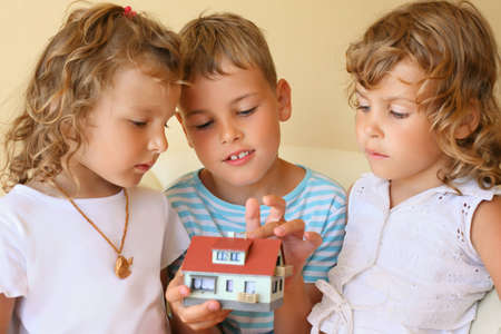 keeping room: children three together keeping in hands model of house in cosy room, boy touches house finger