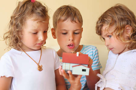 keeping room: children three together keeping in hands model of house in cosy room, two pretty girls and boy  Stock Photo