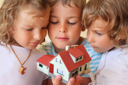 keeping room: children three together keeping in hands model of house in cosy room