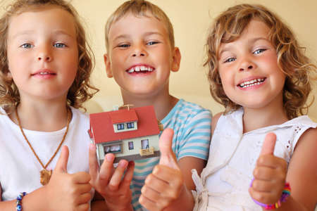 children three together keeping in hands model of house in cosy room, shows �� gesture photo