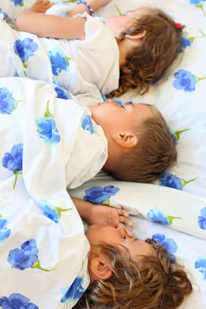 children three together sleeping on bed in cosy room photo