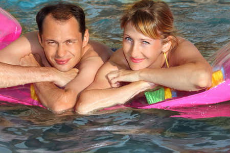 young man and nice women lying on an inflatable mattress in pool, top view Stock Photo - 9265013