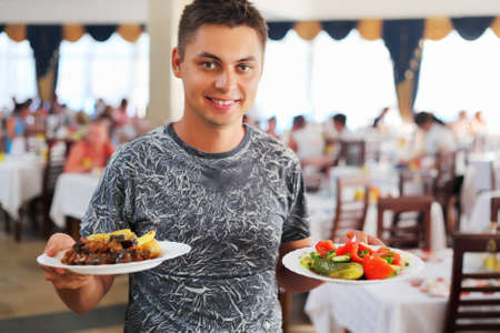 young smiling man with two dishes in hands at restaurant  photo