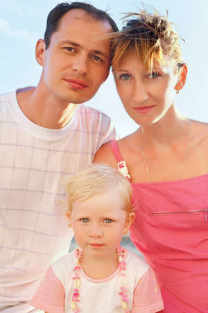 Happy family with little girl on beach, Steadfastly looking photo