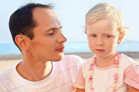 young man with little girl on beach photo