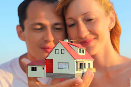Young woman and man keeping in hands model of house with garage photo