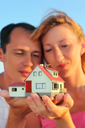 Young woman and man keeping in hands model of house photo