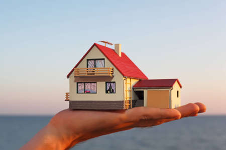 model of house with garage on hand against sea  photo