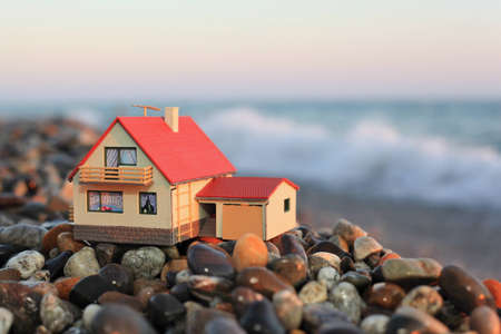 model of house with garage on stony beach in evening photo