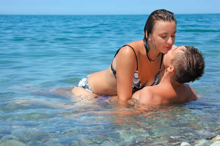 young hot woman sitting astride man in sea near coast, man and  woman kiss