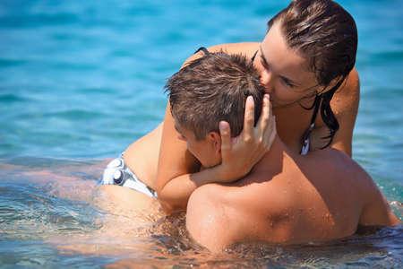 romance sex: young hot woman sitting astride man in sea near coast, woman kisses man  Stock Photo
