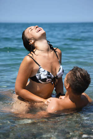 romance sex: young hot woman sitting astride man in sea near coast