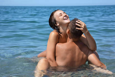 man and woman sex: young hot woman sitting astride man in sea near coast, closed eyes