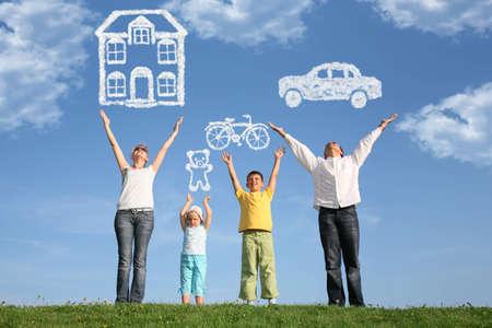 carritos de juguete: familia de cuatro sobre hierba con manos y sue�o Foto de archivo