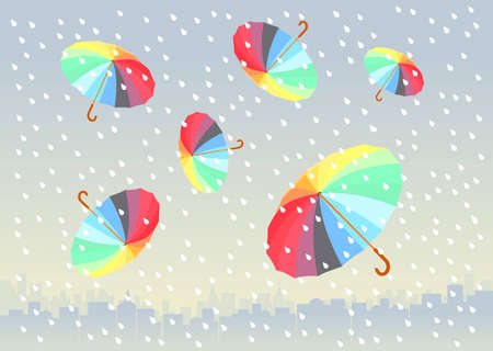 five colorful umbrellas flying under big city. it is raining.