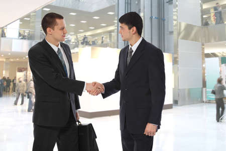 Two young businessmen greet in business centre collage  photo