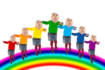iridescent: children with rainbow color dress jumping on rainbow, collage Stock Photo