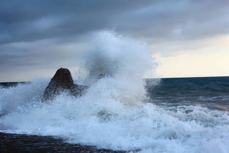 Sea coast with waves breaking about stone photo