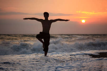 Silhouette guy yoga on sunset wavy beach photo