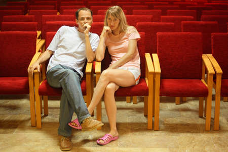 man and woman sitting on a chairs in empty presentation hall. photo