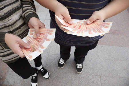 roubles: two teens staying with funs of russian roubles in their hands