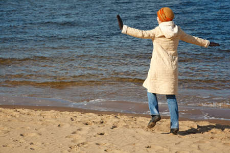 Cheerful girl walks on beach in solar autumn day. In coat, cap and jeans. photo
