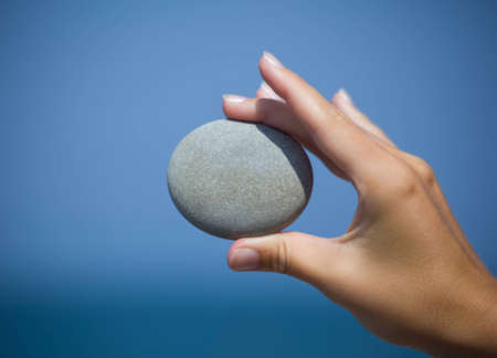 female hand holding pebble against sea, Holds with side