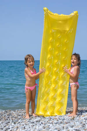 small group of objects: two little girls standing on beach, having control over an inflatable mattress