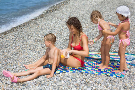 sunburn: young woman and three children smear each other backs with cream for sunburn on stony beach  Stock Photo